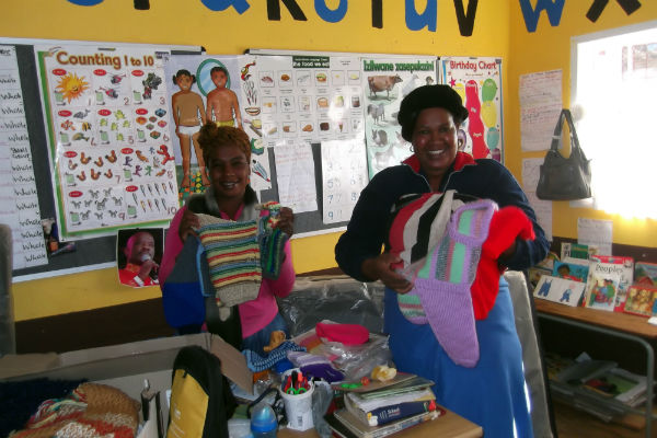 The teachers with the knitwear before giving them to the children